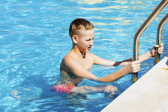 El muchacho deja la piscina después de nadar Fotos de archivo libres de regalías