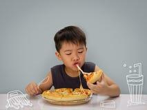 El muchacho del año del asiático 6-7 es feliz a comer la pizza con los wi calientes de un queso foto de archivo
