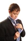 El muchacho del adolescente ata un lazo en un fondo blanco Imagenes de archivo