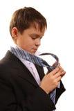 El muchacho del adolescente ata un lazo en un fondo blanco Foto de archivo libre de regalías