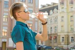 El muchacho del adolescente bebe el agua de la botella en día de verano caliente soleado en la ciudad Foto de archivo