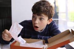 El muchacho del adolescente chocó la expresión después de ve la cuenta para la pizza Imágenes de archivo libres de regalías