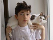 El muchacho del adolescente con el gato en sus hombros se cierra encima de la foto Fotografía de archivo