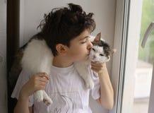 El muchacho del adolescente con el gato en sus hombros se cierra encima de la foto Fotos de archivo