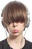 El muchacho del adolescente con el pelo sobre el suyo observa y los auriculares Imagenes de archivo