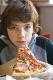 El muchacho del adolescente con la pizza se lleva el restaurante Foto de archivo