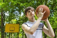 El muchacho del adolescente con una bola para el baloncesto está jugando a baloncesto Foto de archivo libre de regalías