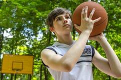 El muchacho del adolescente con una bola para el baloncesto está jugando a baloncesto Fotografía de archivo libre de regalías