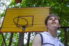 El muchacho del adolescente con una bola para el baloncesto está jugando a baloncesto Imagen de archivo libre de regalías