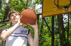 El muchacho del adolescente con una bola para el baloncesto está jugando a baloncesto Fotos de archivo libres de regalías