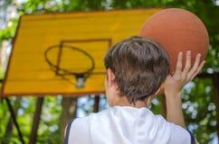 El muchacho del adolescente con una bola para el baloncesto está jugando a baloncesto Imagen de archivo