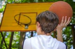 El muchacho del adolescente con una bola para el baloncesto está jugando a baloncesto Imagenes de archivo