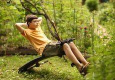 El muchacho del adolescente empuja hacia arriba ejercicios del abdomen de los pilates en instructor portátil Imagenes de archivo