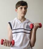 El muchacho del adolescente en una camisa blanca sin las mangas está haciendo ejercicios con pesas de gimnasia Imagen de archivo