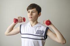 El muchacho del adolescente en una camisa blanca sin las mangas está haciendo ejercicios con pesas de gimnasia Fotos de archivo libres de regalías