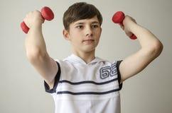 El muchacho del adolescente en una camisa blanca sin las mangas está haciendo ejercicios con pesas de gimnasia Foto de archivo libre de regalías