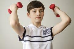 El muchacho del adolescente en una camisa blanca sin las mangas está haciendo ejercicios con pesas de gimnasia Imágenes de archivo libres de regalías