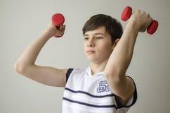 El muchacho del adolescente en una camisa blanca sin las mangas está haciendo ejercicios con pesas de gimnasia Fotografía de archivo