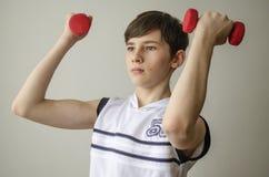 El muchacho del adolescente en una camisa blanca sin las mangas está haciendo ejercicios con pesas de gimnasia Foto de archivo