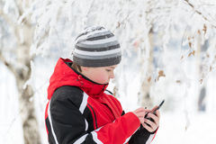 El muchacho del adolescente escribe SMS en parque del invierno Imagenes de archivo