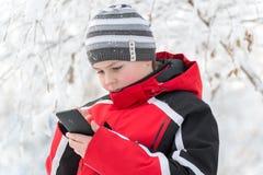 El muchacho del adolescente escribe SMS en parque del invierno Fotos de archivo