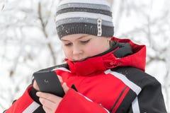El muchacho del adolescente escribe SMS en parque del invierno Imágenes de archivo libres de regalías