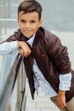 El muchacho del adolescente está esperando las escaleras en la verja Niño de moda en ropa elegante de la ciudad Fotografía de archivo