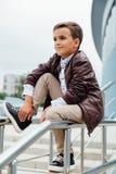 El muchacho del adolescente está esperando las escaleras en la verja Niño de moda en ropa elegante de la ciudad Imagen de archivo libre de regalías