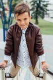 El muchacho del adolescente está esperando las escaleras en la verja Niño de moda en ropa elegante de la ciudad Imágenes de archivo libres de regalías