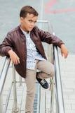 El muchacho del adolescente está esperando las escaleras en la verja Niño de moda en ropa elegante de la ciudad Foto de archivo libre de regalías