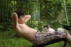 El muchacho del adolescente hace ejercicios de estómago con el gato Imágenes de archivo libres de regalías