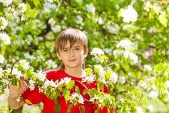 El muchacho del adolescente lleva a cabo la rama con las flores blancas Foto de archivo libre de regalías
