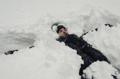 El muchacho del adolescente miente en nieve profunda debajo de las nevadas pesadas Fotos de archivo libres de regalías