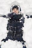 El muchacho del adolescente miente en nieve profunda debajo de las nevadas pesadas Imagen de archivo