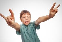 El muchacho del adolescente muestra al diablo de la roca del metal de las manos del gesto Foto de archivo libre de regalías
