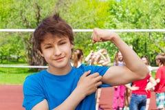 El muchacho del adolescente muestra los músculos del bíceps en el patio Fotografía de archivo libre de regalías