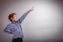 El muchacho del adolescente muestra su mano para arriba en fondo gris Imagen de archivo