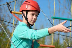 El muchacho del adolescente mueve la rejilla vertical en la carrera de obstáculos en el parque de atracciones, actividades al air Foto de archivo libre de regalías