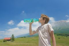 El muchacho del adolescente que bebe el agua clara de la batalla en el suyo da alto en las montañas Imagenes de archivo