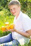 El muchacho del adolescente se está sosteniendo de cristal con el zumo de naranja Fotos de archivo libres de regalías