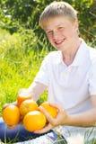 El muchacho del adolescente se está sosteniendo de cristal con el zumo de naranja Imagenes de archivo