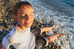 El muchacho del adolescente se sienta en la costa de piedra, ojos cerrados Imagen de archivo libre de regalías