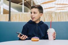 El muchacho del adolescente se sienta en la tabla en café, bebe el batido de leche, come el buñuelo, smartphone de los controles  Imágenes de archivo libres de regalías