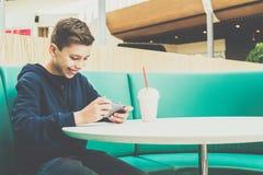 El muchacho del adolescente se sienta en la tabla en café, bebe el batido de leche y utiliza smartphone El muchacho juega a juego Foto de archivo