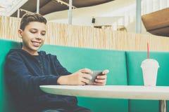 El muchacho del adolescente se sienta en la tabla en café, bebe el batido de leche y utiliza smartphone El muchacho juega a juego Fotos de archivo libres de regalías