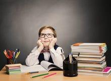 El muchacho del alumno en vidrios piensa la sala de clase, libro de los estudiantes del niño