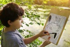 El muchacho del artista del adolescente hace el bosquejo del proyecto del lago de la charca en el bosque Fotografía de archivo