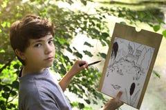El muchacho del artista del adolescente hace el bosquejo del proyecto del lago de la charca en el bosque Imágenes de archivo libres de regalías