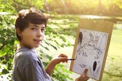 El muchacho del artista del adolescente hace el bosquejo del proyecto del lago de la charca en el bosque Fotos de archivo