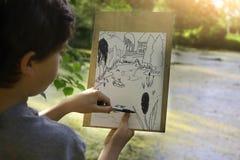 El muchacho del artista del adolescente hace el bosquejo del proyecto del lago de la charca en el bosque Imagen de archivo